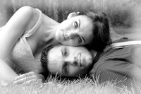 Black and White version of a young couple laying on the grass wi